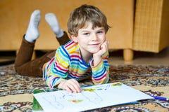 Peuterjong geitjejongen die thuis thuiswerk maken, die een verhaal met kleurrijke pennen schilderen Stock Foto's