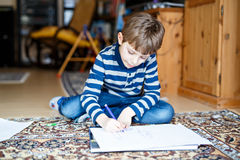 Peuterjong geitjejongen die thuis thuiswerk maken, die een verhaal met kleurrijke pennen schilderen Royalty-vrije Stock Fotografie