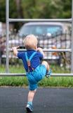 Peuterjongen bij speelplaats die borrels en bretels dragen Stock Foto's