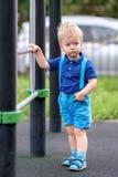 Peuterjongen bij speelplaats die borrels en bretels dragen Stock Fotografie