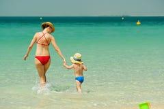 Peuterjongen die op strand met moeder lopen Stock Afbeelding