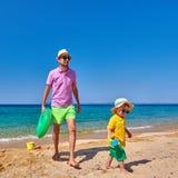 Peuterjongen die op strand met vader lopen stock afbeelding