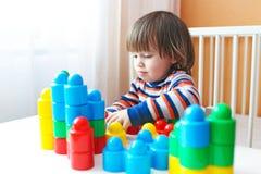 Peuterjongen die plastic blokken thuis spelen Stock Foto's