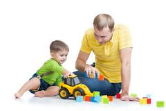 Peuterjongen en zijn het stuk speelgoed van de vaderreparatie tractor Stock Foto's