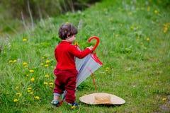 Peuterjongen met paraplu en hoed op een gras stock afbeeldingen