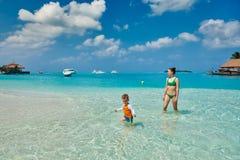 Peuterjongen op strand met moeder stock foto