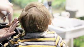 Peuterkind die zijn eerste kapsel krijgen stock footage