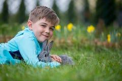 Peuterkind, leuke jongen, die met weinig konijn in openlucht spelen royalty-vrije stock foto