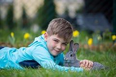 Peuterkind, leuke jongen, die met weinig konijn in openlucht spelen stock foto