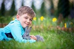 Peuterkind, leuke jongen, die met weinig konijn in openlucht spelen stock afbeelding