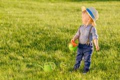 Peuterkind in openlucht De jongen die van de één éénjarigebaby strohoed dragen die gieter met behulp van Stock Afbeeldingen