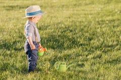 Peuterkind in openlucht De jongen die van de één éénjarigebaby strohoed dragen die gieter met behulp van Royalty-vrije Stock Fotografie