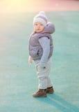 Peuterkind in warm vestjasje in openlucht Babyjongen bij speelplaats tijdens zonsondergang Stock Afbeelding