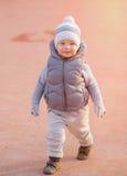 Peuterkind in warm vestjasje in openlucht Babyjongen bij speelplaats tijdens zonsondergang Stock Fotografie