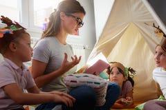 Peuterleraar die een verhaal lezen aan kinderen bij kleuterschool royalty-vrije stock afbeelding