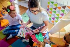 Peuterleraar die een verhaal lezen aan kinderen bij kleuterschool stock afbeeldingen