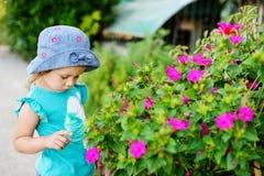 Peutermeisje dichtbij bloemen Royalty-vrije Stock Afbeeldingen