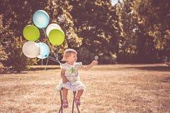 Peutermeisje het spelen met ballons en bellen stock afbeelding