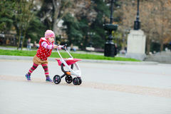 Peutermeisje met stuk speelgoed wandelwagen Royalty-vrije Stock Foto