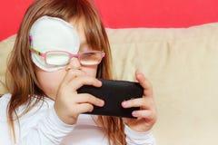 Peutermeisje met verband op oog speelspelen stock foto