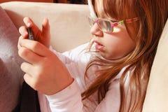 Peutermeisje met verband op oog speelspelen stock afbeelding