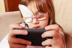 Peutermeisje met verband op oog speelspelen stock afbeeldingen