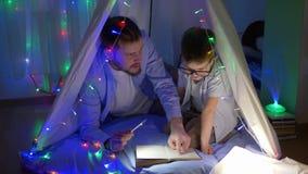 Peuteronderwijs, jonge vader met de sprookjes van de flitslichtlezing aan jongen die in glazen in tent met slingers zitten stock videobeelden