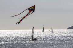 A kite flies high above the yachts sailing off Beachy Head near Eastbourne in East Sussex, England royalty free stock images