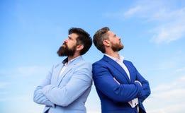 Pewny znak ty musisz ufać partnera biznesowego Mężczyzna formalni kostiumy stoją z powrotem popierać niebieskiego nieba tło ufny obrazy stock