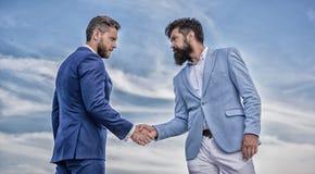 Pewny znak ty musisz ufa? partnera biznesowego Mężczyzn formalni kostiumy trząść ręki niebieskiego nieba tło Transakcja biznesowa fotografia stock