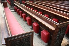 Pews in Bath Abbey. Raws of pews in Bath Abbey, Somerset, England. Wooden benches with carved back and sides and red leather seats, aisles visible Stock Photos