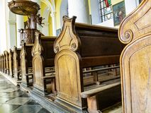 The pews of Church of St. Sebastian in Stavelot, Belgium, bench end close view, the pulpit in the background. STAVELOT, BELGIUM - APRIL 02, 2014: The pews of stock photography