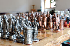 Pewter chess pieces on board. Pewter chess pieces on wood board Stock Images