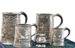 Pewter drinking mugs with measure. Old pewter ale jars of different sizes Stock Image