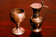 Pewter Goblet & Jug. Antique pewter goblet and wine jug on table Stock Images