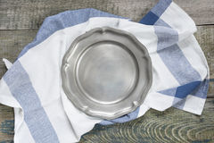 Pewter plate on a rough wooden table. Empty pewter plate and kitchen towel on a rough wooden table, top view Royalty Free Stock Images