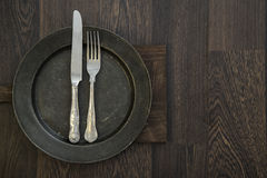 Pewter plate and vintage cutlery on rustic dark wooden backgroun. Pewter plate and vintage cutlery on rustic wooden background Royalty Free Stock Photo