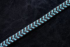 Peyote choker necklace made of seed beads on a dark background. Close up royalty free stock image