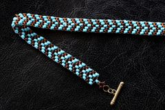 Peyote choker necklace made of seed beads on a dark background. Close up royalty free stock photography