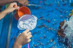 Pez de colores que saca con pala con los niños en festival anual imagenes de archivo