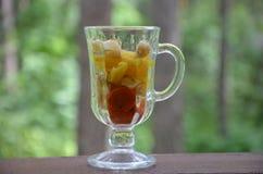 Pezzi affettati di frutta e di verdure in una tazza di vetro con una maniglia Frutta della disintossicazione Insalate sane casali Fotografie Stock