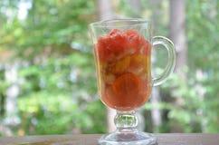 Pezzi affettati di frutta e di verdure in una tazza di vetro con una maniglia Frutta della disintossicazione Insalate sane casali Fotografia Stock
