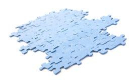 Pezzi blu collegati di puzzle isolati Fotografia Stock