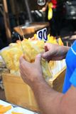 Pezzi d'acquisto dell'ananas dell'uomo, Tailandia Fotografie Stock