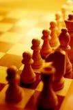 Pezzi degli scacchi alla luce ambientale gialla Fotografie Stock