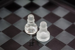 Pezzi degli scacchi fatti di vetro: un confronto fra due pegni contro un fondo nero Fotografie Stock