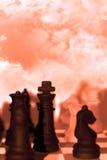 Pezzi degli scacchi isolati contro il cielo rosso Immagini Stock