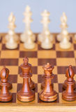 Pezzi degli scacchi nella posizione di partenza su un bordo di legno Fotografia Stock Libera da Diritti