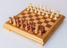 Pezzi degli scacchi nella posizione di partenza su un bordo di legno Immagine Stock Libera da Diritti