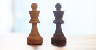 Pezzi degli scacchi scuri, colore marrone chiaro Chiuda sul punto di vista di re con i dettagli Priorità bassa vaga Fotografia Stock
